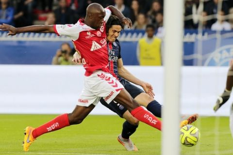 PSG soccer player Edinson Cavani, background center, challenges for the ball with Reims' Antoine Conte, during the French League One soccer Match between Paris Saint-Germain and Stade de Reims, at the Parc des Princes stadium in Paris, Saturday, May 23, 2015. Paris Saint-Germain clinched a third straight title. (AP Photo/Jacques Brinon)