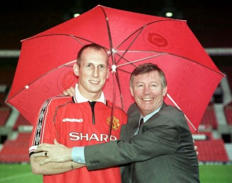 Something for a rainy day : Jaap Stam signs for Manchester United for a fee of  10 million pounds and makes manager Alex Ferguson a happyman. Photo by Dave Kendall/PA.