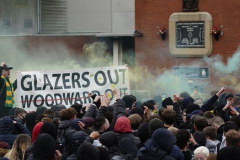 Manchester United fans hold up a banner as they protest against the Glazer family, the American owners of Manchester United, before their English Premier League soccer match against Liverpool at Old Trafford stadium in Manchester, England, Thursday, May 13, 2021. (AP Photo/Jon Super)