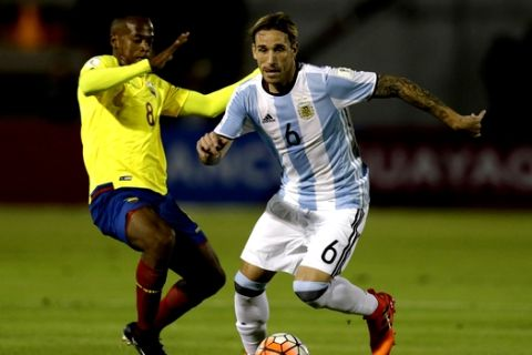 Argentina's Lucas Biglia, right, fights for the ball against Ecuador's Romario Ibarra during their 2018 World Cup qualifying soccer match at the Atahualpa Olympic Stadium in Quito, Ecuador, Tuesday, Oct. 10, 2017. (AP Photo/Dolores Ochoa)