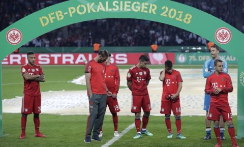 Bayern players stand on the pitch after the German soccer cup final match between FC Bayern Munich and Eintracht Frankfurt in Berlin, Germany, Saturday, May 19, 2018. (AP Photo/Michael Sohn)