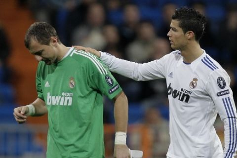 Real Madrid's goalkeeper Jerzy Dudek from Poland, left is consoled by Cristiano Ronaldo from Portugal as he leaves the pitch injured during a Group G Champions League soccer match against Auxerre at the Santiago Bernabeu stadium in Madrid, Wednesday Dec. 8, 2010. (AP Photo/Paul White)