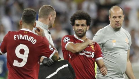Liverpool's Mohamed Salah grimaces as he leaves after injuring himself during the Champions League Final soccer match between Real Madrid and Liverpool at the Olimpiyskiy Stadium in Kiev, Ukraine, Saturday, May 26, 2018 (AP Photo/Matthias Schrader)