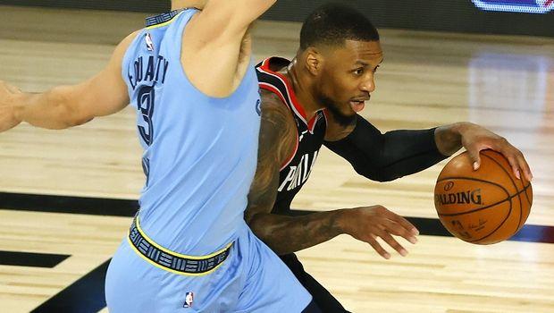 Portland Trail Blazers' Damian Lillard, right, drives past Memphis Grizzlies' Grayson Allen during the first half of an NBA basketball game Saturday, Aug. 15, 2020, in Lake Buena Vista, Fla. (Kevin C. Cox/Pool Photo via AP)