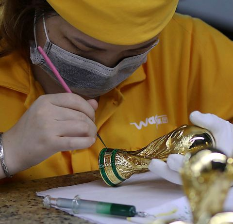 In this June 11, 2018, photo, a worker paints on a miniature FIFA World Cup trophies at a factory in Dongguan in south China's Guangdong province. The 21st World Cup begins on Thursday, June 14, 2018, when host Russia takes on Saudi Arabia. (Color China Photo via AP)