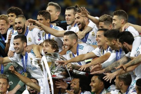 Real Madrid players celebrate with the trophy after winning the Champions League Final soccer match between Real Madrid and Liverpool at the Olimpiyskiy Stadium in Kiev, Ukraine, Saturday, May 26, 2018. (AP Photo/Sergei Grits)