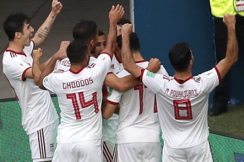 Players of Iran celebrate the opening goal during the group B match between Morocco and Iran at the 2018 soccer World Cup in the St. Petersburg Stadium in St. Petersburg, Russia, Friday, June 15, 2018. (AP Photo/Darko Vojinovic)