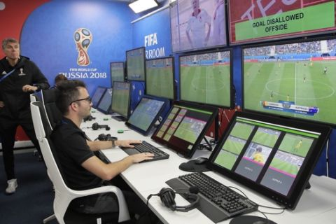 VAR refereeing Project Leader Roberto Rosetti, left, demonstrates a video operation room (VOR), a facility of the Video Assistant Referee (VAR) system which will be rolled out for the first time during theWorld Cup, at the 2018 World Cup International Broadcast Centre in Moscow, Russia, Saturday, June 9, 2018. (AP Photo/Dmitri Lovetsky)