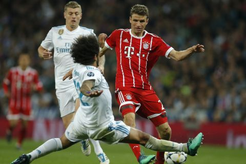 Real Madrid's Marcelo blocks a shot by Bayern's Thomas Mueller, right, during the Champions League semifinal second leg soccer match between Real Madrid and FC Bayern Munich at the Santiago Bernabeu stadium in Madrid, Spain, Tuesday, May 1, 2018. (AP Photo/Paul White)