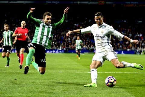 Real Madrid's Cristiano Ronaldo, right, challenges Real Betis' Alin Tosca during a Spanish La Liga soccer match between Real Madrid and Real Betis at the Santiago Bernabeu stadium in Madrid, Sunday, March 12, 2017. Ronaldo scored once in Real Madrid's 2-1 victory. (AP Photo/Francisco Seco)