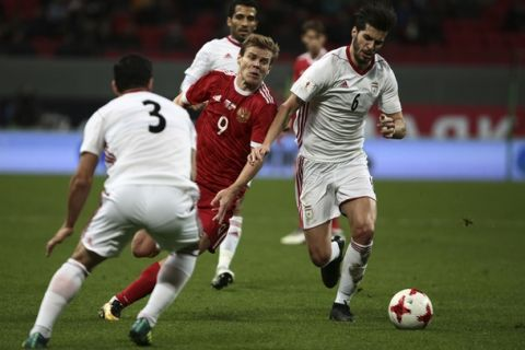 Iran's Saeid Ezatolahi, right, Ehsan Hajsafi, left, and Russia's Alexander Kokorin compete for the ball, during the friendly soccer match between Russia and Iran, in Kazan, Russia, Tuesday, Oct. 10, 2017. (AP Photo/Nikolay Alexandrov)