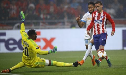 Atletico's Antoine Griezmann, right, scores 2-0 passing Marseille's goalkeeper Steve Mandanda, left, and Marseille's Jordan Amavi, second right, during the Europa League Final soccer match between Marseille and Atletico Madrid at the Stade de Lyon in Decines, outside Lyon, France, Wednesday, May 16, 2018. (AP Photo/Francois Mori)