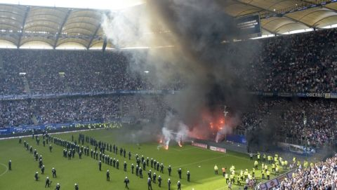 Police officers and security staff stand on the pitch when supporters light fireworks just before the end of the German Bundesliga soccer match between Hamburger SV and Borussia Moenchengladbach in Hamburg, northern Germany, Saturday, May 12, 2018 when Hamburg relegated for the first time in the history of the German Bundesliga.  (Axel Heimken/dpa via AP)