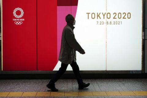 Πολίτης στο Τόκιο περπατάει μπροστά από την επιγραφή των Ολυμπιακών Αγώνων