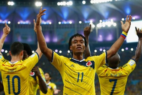 RIO DE JANEIRO, BRAZIL - JUNE 28: Juan Guillermo Cuadrado of Colombia celebrates his team's second goal scored by James Rodriguez (L) during the 2014 FIFA World Cup Brazil round of 16 match between Colombia and Uruguay at Maracana on June 28, 2014 in Rio de Janeiro, Brazil.  (Photo by Clive Rose/Getty Images)