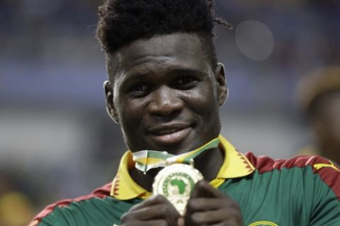 Cameroon's Robert Ndip Tambe shows off his medal after winning the African Cup of Nations final soccer match between Egypt and Cameroon at the Stade de l'Amitie, in Libreville, Gabon, Sunday, Feb. 5, 2017. Cameroon won 2-1. (AP Photo/Sunday Alamba)