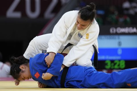 Elisavet Teltsidou of Greece, top, and Sun Xiaoqian of China compete during the women -70kg elimination round of the judo match at the 2020 Summer Olympics in Tokyo, Japan, Wednesday, July 28, 2021. (AP Photo/Vincent Thian)