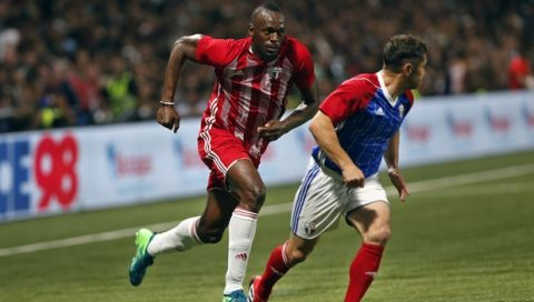 Former Olympic and Jamaican sprinter Usain Bolt, left, challenges for the ball with France's Bixente Lizarazu during a charity soccer match between members of the 1998 World Cup winning French team and a team of international veteran players who were also involved in the same tournament, at the U Arena in Nanterre, north of Paris, France, Tuesday, June 12, 2018. (AP Photo/Thibault Camus)