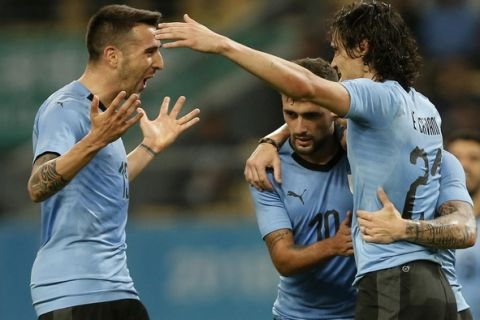 Uruguay's Edinson Cavani, right, celebrates with teammates Giorgian De Arrascaeta, center, and Matias Vecino, left, after scoring a goal against the Czech Republic during their match in the 2018 China Cup International Football Championship in Nanning in southern China's Guangxi province, Friday, March 23, 2018. (Color China Photo via AP)