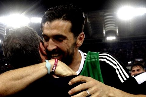 Juventus goalkeeper Gianluigi Buffon celebrates with a team staffer at the end of the Serie A soccer match between Roma and Juventus, at the Rome Olympic stadium, Sunday, May 13, 2018. The match ended in a scoreless draw and Juventus won record-extending seventh straight Serie A title. (AP Photo/Gregorio Borgia)