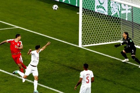 Serbia's Aleksandar Mitrovic, left, heads the ball to score the opening goal during the group E match between Switzerland and Serbia at the 2018 soccer World Cup in the Kaliningrad Stadium in Kaliningrad, Russia, Friday, June 22, 2018. (AP Photo/Antonio Calanni)