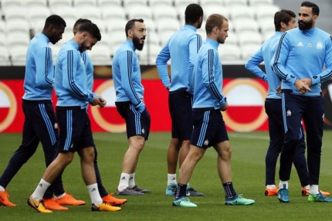 The Olympique Marseille (OM) soccer team with Konstantínos Mítroglou, right, walk, during a training session, at the Groupama stadium in Decines, outside Lyon, central France, Tuesday, May 15, 2018. Marseille will play Atletico Madrid in the Europa League final on Wednesday. (AP Photo/Laurent Cipriani)