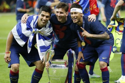 Barcelona's Lionel Messi, centre, Neymar and Luis Suarez, left, celebrate with the trophy after after the Champions League final soccer match between Juventus Turin and FC Barcelona at the Olympic stadium in Berlin Saturday, June 6, 2015. Barcelona won the match 3-1.  (AP Photo/Frank Augstein)