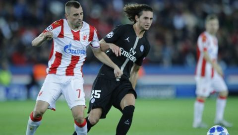 PSG midfielder Adrien Rabiot, right, is challenged by Red Star's Nenad Krsticic during the group C Champions League soccer match between Paris Saint Germain and Red Star Belgrade at the Parc des Princes stadium in Paris, France, Wednesday, Oct. 3, 2018. (AP Photo/Francois Mori)