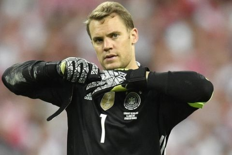 Germany goalkeeper Manuel Neuer takes off his gloves at the end of the Euro 2016 Group C soccer match between Germany and Poland at the Stade de France in Saint-Denis, north of Paris, France, Thursday, June 16, 2016. (AP Photo/Martin Meissner)