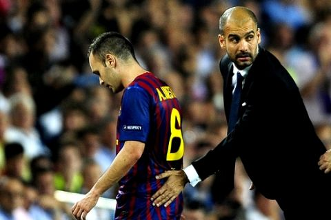 FC Barcelona's Andres Iniesta, left, walks to the bench after been injured, accompanied  his coach Pep Guardiola,  during a Champions league soccer match against AC Milan at the Nou Camp stadium in Barcelona, Spain, Tuesday, Sept. 13, 2011. (AP Photo/Manu Fernandez)
