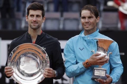 Rafael Nadal, right, of Spain and Novak Djokovic of Serbia pose with their trophies at the end of their final match at the Italian Open tennis tournament, in Rome, Sunday, May 19, 2019. (AP Photo/Gregorio Borgia)