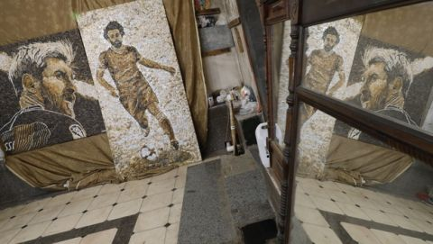 The pebble mosaics featuring Argentina's Lionel Messi and Egypt's Mohammed Salah created by local artist Anna Solnechnaya and het apprentices are placed at Solnechnaya's workshop ahead of the 2018 soccer World Cup in Kazan, Russia, Wednesday, June 13, 2018. The portraits currently are exhibited on the streets. Kazan is one of World Cup match venues in Russia. (AP Photo/Eugene Hoshiko)