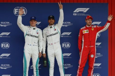Mercedes driver Lewis Hamilton of Britain, center, pole position, is flanked by his teammate Valtteri Bottas of Finland, second fastest time, and Ferrari driver Sebastian Vettel of Germany, right, third fastest time after the qualifying session for the Spanish Formula One Grand Prix at the Barcelona Catalunya racetrack in Montmelo, Spain, Saturday, May 12, 2018. The Spanish Formula One Grand Prix will take place on Sunday. (AP Photo/Manu Fernandez)