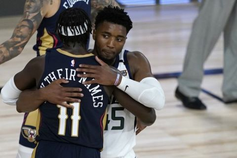 Utah Jazz's Donovan Mitchell (45) and New Orleans Pelicans' Jrue Holiday (11) hug following an NBA basketball game Thursday, July 30, 2020, in Lake Buena Vista, Fla. The Jazz won 106-104. (AP Photo/Ashley Landis, Pool)
