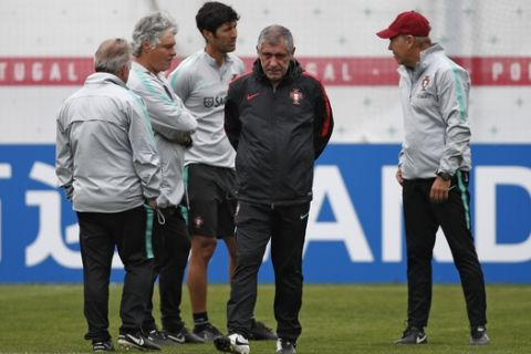 Portugal head coach Fernando Santos, front, walks along the pitch during the training session of Portugal at the 2018 soccer World Cup in Kratovo, outskirts Moscow, Russia, Wednesday, June 13, 2018. (AP Photo/Francisco Seco)