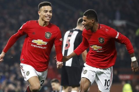 Manchester United's Mason Greenwood celebrates scoring his side's second goal of the game with teammate Marcus Rashford during their English Premier League soccer match against Newcastle United at Old Trafford, Manchester, England, Thursday, Dec. 26, 2019. (Martin Rickett/PA via AP)