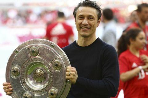Bayern coach Niko Kovac lifts the trophy after winning Bayern's 7th straight Bundesliga title after the German Soccer Bundesliga match between FC Bayern Munich and Eintracht Frankfurt in Munich, Germany, Saturday, May 18, 2019. (AP Photo/Matthias Schrader)