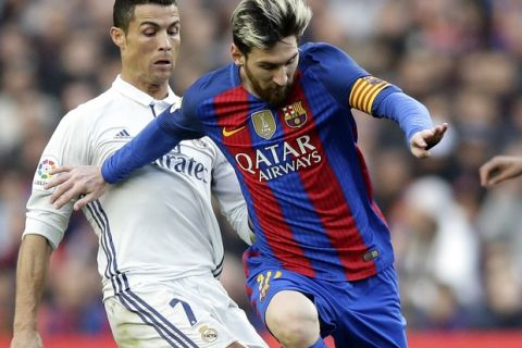 Barcelona's Lionel Messi, right, escapes Real Madrid's Cristiano Ronaldo during the Spanish La Liga soccer match between FC Barcelona and Real Madrid at the Camp Nou in Barcelona, Spain, Saturday, Dec. 3, 2016. (AP Photo/Manu Fernandez)