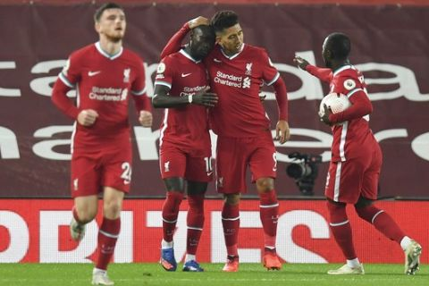 Liverpool's Sadio Mane, second lefties congratulated by teammates after scoring his team's first goal during the English Premier League soccer match between Liverpool and Arsenal at Anfield in Liverpool, England, Monday, Sept. 28, 2020. (Paul Ellis/Pool via AP)
