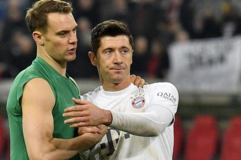Bayern's goalkeeper Manuel Neuer, left, hugs team mate Robert Lewandowski after the German Bundesliga soccer match between Fortuna Duesseldorf and FC Bayern Munich in Duesseldorf, Germany, Saturday, Nov. 23, 2019. (AP Photo/Martin Meissner)