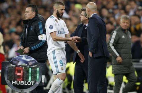 Real Madrid's Karim Benzema leaves the pitch besides coach Zinedine Zidane during the Champions League semifinal second leg soccer match between Real Madrid and FC Bayern Munich at the Santiago Bernabeu stadium in Madrid, Spain, Tuesday, May 1, 2018. (AP Photo/Francisco Seco)