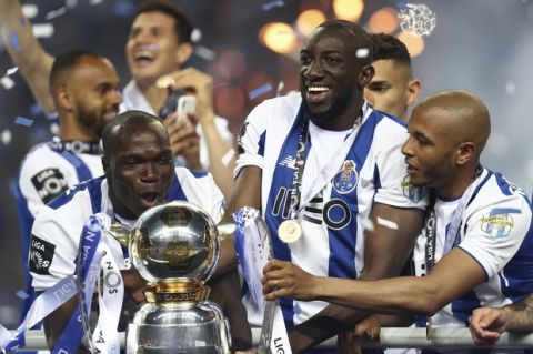 Porto's Vincent Aboubakar, Moussa Marega and Yacine Brahimi, from left to right, celebrate with the trophy at the end of the Portuguese league soccer match between FC Porto and Feirense at the Dragao stadium in Porto, Portugal, Sunday, May 6, 2018. Porto clinched the league title Saturday night, two rounds before the end, when Benfica and Sporting CP tied 0-0 in their Lisbon derby. (AP Photo/Luis Vieira)
