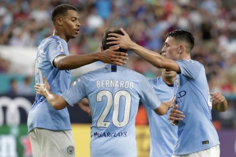 Manchester City midfielder Bernardo Silva (20) is congratulated by teammates after scoring a goal during the first half of an International Champions Cup tournament soccer match against FC Bayern, Saturday, July 28, 2018, in Miami Gardens, Fla. (AP Photo/Lynne Sladky)