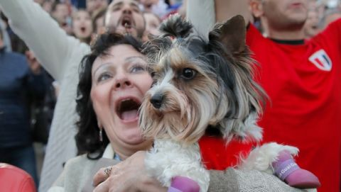 A woman screams holding a small dog as fans celebrate after Russia scored the third goal during the opening match of the 2018 soccer World Cup, between Russia and Saudi Arabia, in the fan zone in Yekaterinburg, Russia, Thursday, June 14, 2018. (AP Photo/Vadim Ghirda)