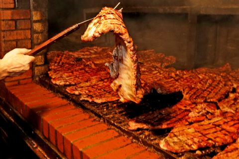 Republican presidential candidate Wisconsin Gov. Scott Walker helps Enrique Rivas turn over a slab of ribs at Dreamland BBQ during a campaign stop, Saturday, Aug. 22, 2015, in Birmingham, Ala. (AP Photo/Butch Dill)