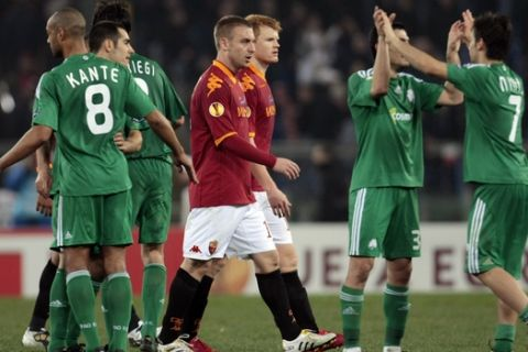 Panathinaikos' players, in green, celebrate past AS Roma's Daniele De Rossi, at center in foreground red jersey, and teammate John Arne Riise at the end of the UEFA Europa League round of 32 second leg soccer match between AS Roma and Panathinaikos, in Rome, Thursday, Feb. 25, 2010. Panathinaikos won 3-2.  (AP Photo/Gregorio Borgia)