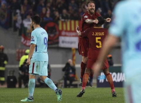 Barcelona's Luis Suarez walks off the pitch as Roma players Daniele De Rossi and Juan Jesus celebrate reaching the semifinals after the Champions League quarterfinal second leg soccer match between between Roma and FC Barcelona, at Rome's Olympic Stadium, Tuesday, April 10, 2018. (AP Photo/Gregorio Borgia)