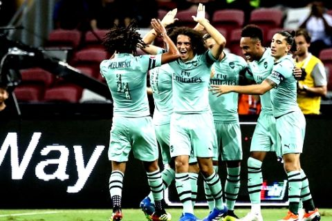 Arsenal players celebrate after Mesut Oil scored their first goal during the International Champions Cup match between Arsenal and Paris Saint-Germain in Singapore, Saturday, July 28, 2018. (AP Photo/Yong Teck Lim)