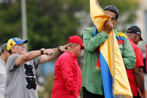 Venezuela's President Nicolas Maduro kisses his country's flag as Argentina's former soccer player Diego Maradona points during a closing campaign rally in Caracas, Venezuela, Thursday, May 17, 2018. Maduro is seeking a new six-year mandate and despite crippling hyperinflation and widespread shortages of food and medicine, he is widely expected to win the May 20 election, that opponents have denounced as a fraud and have been condemned by much of the international community. (AP Photo/Ariana Cubillos)