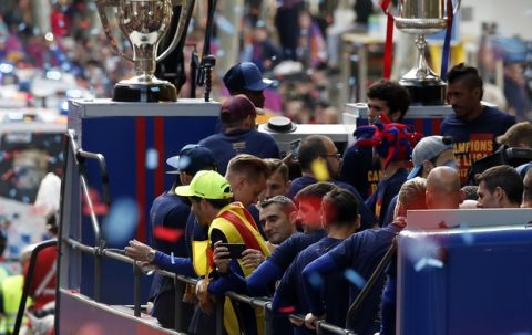 Barcelona coach Ernesto Valverde, center, takes pictures from a bus with players celebrating during a street parade in Barcelona, Spain, Monday April 30, 2018, after winning the Spanish La Liga soccer title. Barcelona clinched the 2017/18 Spanish soccer league title after a 4-2 win at Deportivo La Coruna on Sunday. (AP Photo/Manu Fernandez)